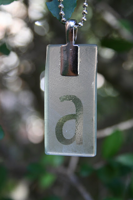 An etched monogram pendant