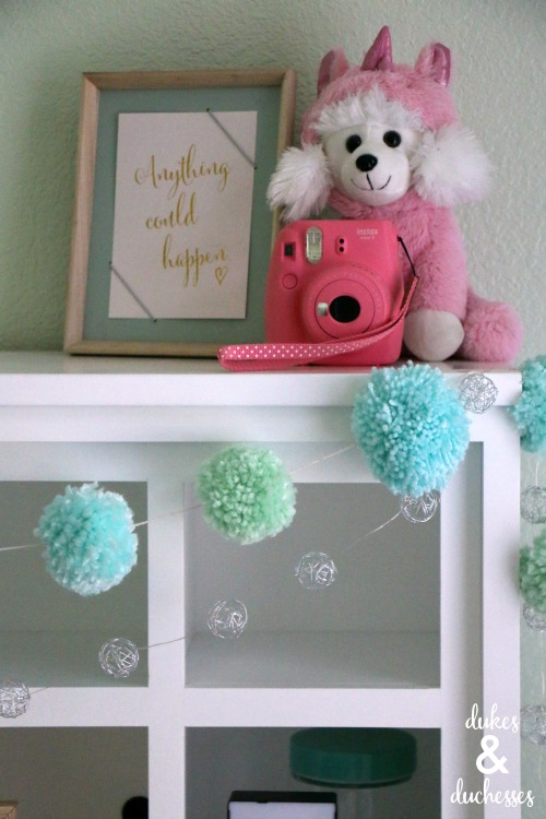DIY yarn pom pom garland on headboard